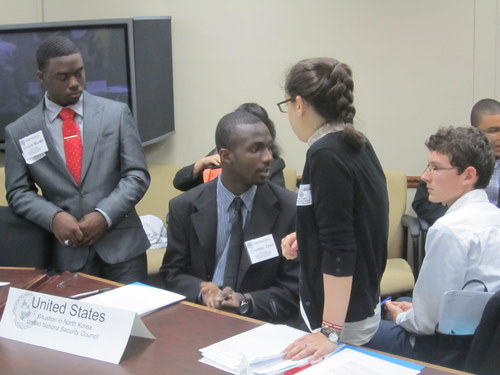 High school delegates discuss global issues facing refugees and immigrants in the Human Rights Council