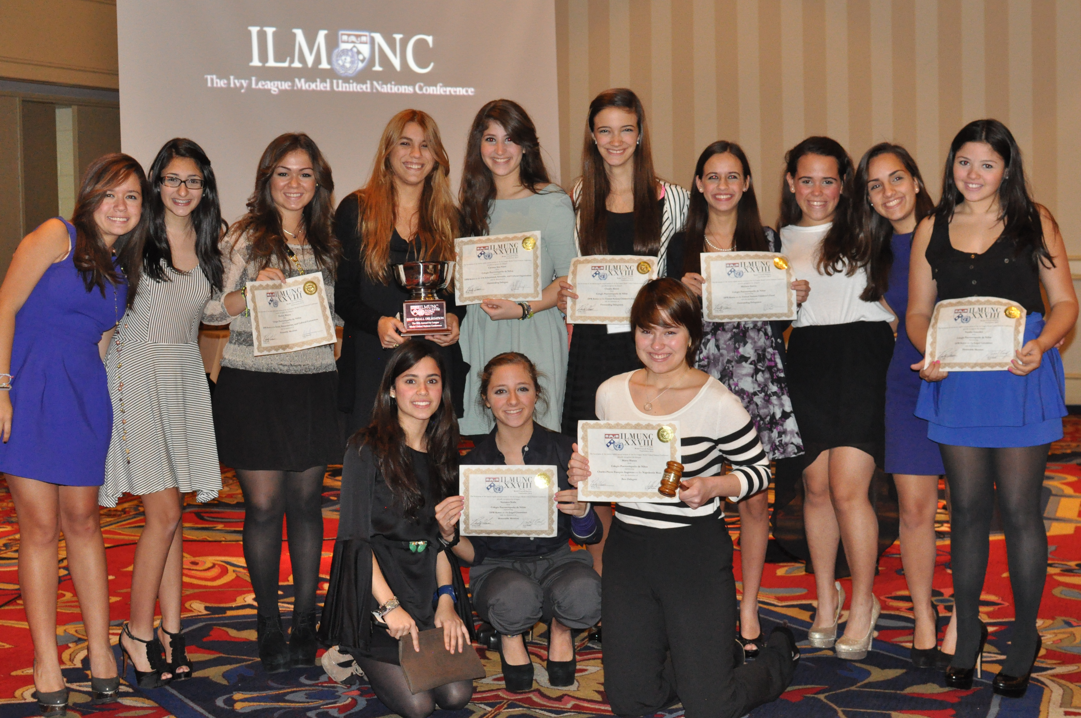 colegio de nias proudly holds up their best small delegation award at ilmunc