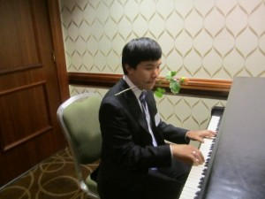 A delegate plays on a piano sitting in the hall after committee ends for the day