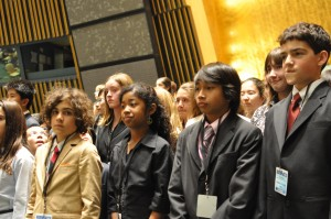 Students representing different countries stand inside the United Nations General Assembly Hall during Opening Ceremonies