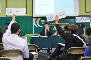 The Chair of the International Drug Control Treaty 2012 looks to select the next speaker. Note the Spanish names for the countries on the placards and the Spanish text in the draft resolution projected in the back.