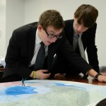 Two crisis staffers examine a map of military operations.