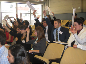 Enthusiastic delegates in the Clinton Global Initiative raise their placards.