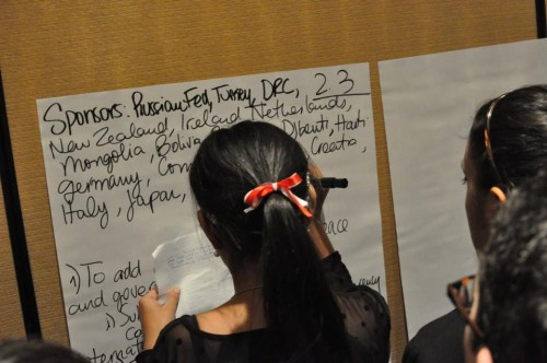 Delegates writing amendments on big post-it notes
