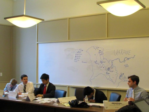 Delegates analyze a detailed map of the contested region provided by the Ad-Hoc crisis staff.