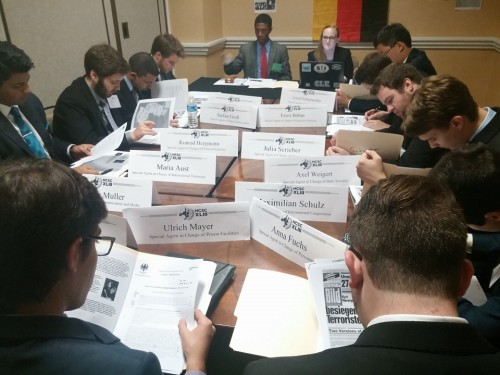 Delegates reading their news updates in the Ad Hoc Committee